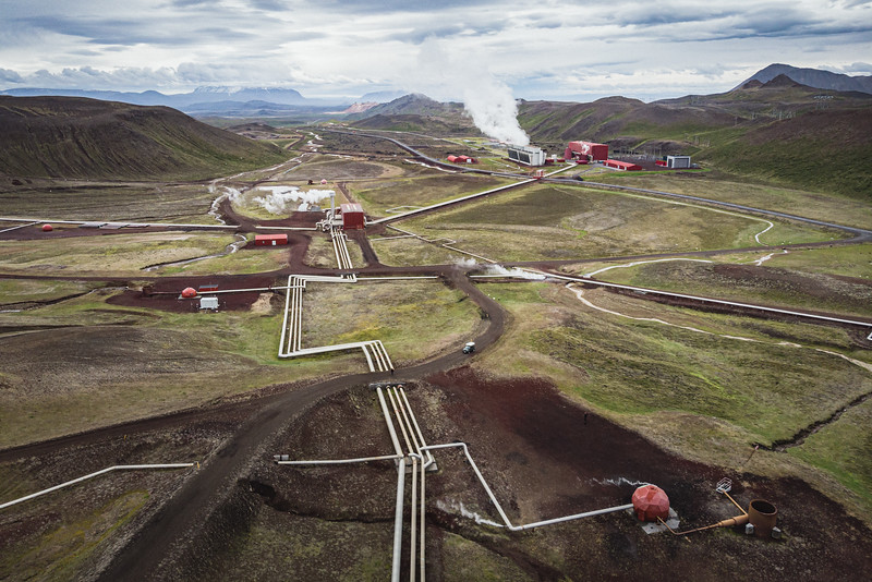 Geothermal wells and pipes in Krafla geothermal power station, in northern Iceland. Geothermal energy is a renewable energy source with a low environmental impact compared to fossil fuel power plants. The exploitation of geothermal resources may lead to greenhouse gases emission, but all carbon emissions from the Krafla Power Station are substantially reduced by reinjecting back into the geothermal wells or reutilising the carbon dioxide emitted from geothermal gas to ensure the least impact on the environment. In 2020 about 50,000 tonnes of CO2 were injected back into the geothermal reservoir. The gases react with basaltic subsurface rocks to form stable minerals for safe, long-term storage of the injected gases.