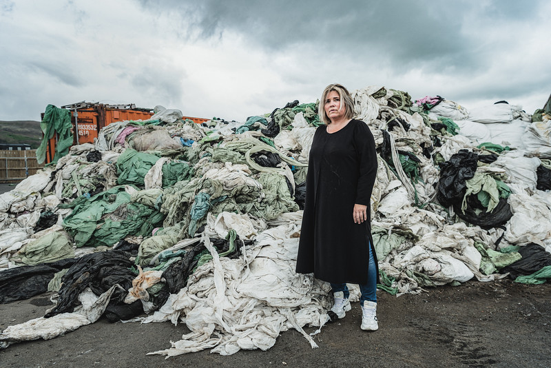 "Aslaug (Asa), co-founder of Pure North Recycling, in front of disposed plastic ready to be recycled. ""This is our money"", Asa said in front of this plastic garbage. The company implements a process that allows recycling plastic completely without using any chemicals, but only steam, water, and electricity provided by the geothermal plant. Plastic processed by their facility is turned into a raw material that is then sold to companies that make new products from it."