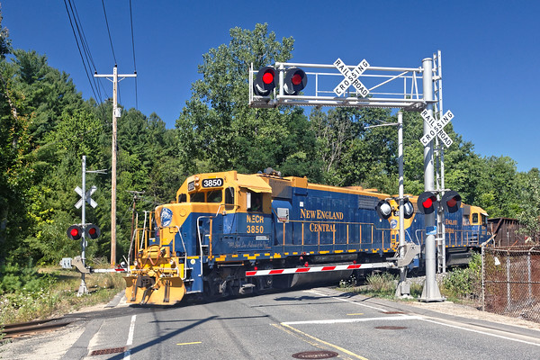 On a crystal clear summer day, NECR train 610 heads south with 5 cars at Hospital crossing in Palmer, MA.<br /> 7/27/2016 - 598C2275d2K