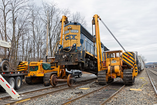 """...Glad we've got triple A...""<br /> CSX GP40-2, no. 6207 broke an axle yesterday as it crossed the diamond at MP83 in Palmer MA. She was dragged onto one of the siding tracks in the CSX yard in Palmer for repairs and she's been hanging in the air for a while as the repair crew waits for parts to come from Selkirk.<br /> 12/8/2017 - 598C4811dK"