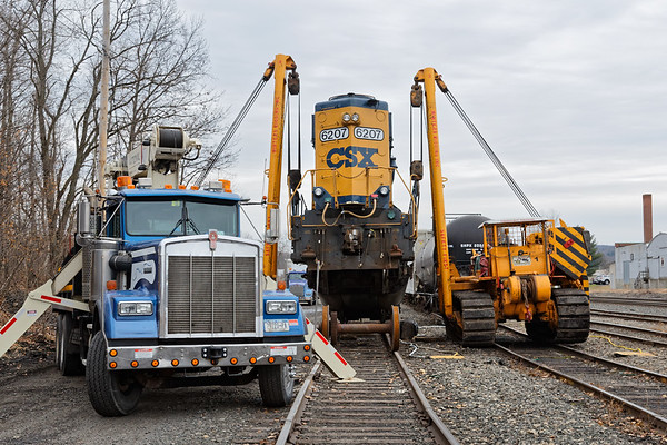 """""""...Glad we've got triple A...""""<br /> CSX GP40-2, no. 6207 broke an axle yesterday as it crossed the diamond at MP83 in Palmer MA. She was dragged onto one of the siding tracks in the CSX yard in Palmer for repairs and she's been hanging in the air for a while as the repair crew waits for parts to come from Selkirk.<br /> 12/8/2017 - 598C4805dK"""