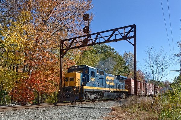 With a background of early season color, Pan Am switcher FI-1 heads west under the ancient signal bridge at Parkers in Gardner MA. 10/19/2017 - 598C4179d2K