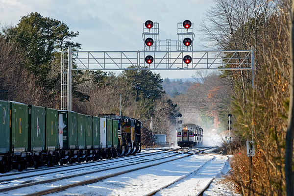 """In Ayer MA, intermodal train 23K holds the """"Camp"""" track as an inbound """"T"""" commuter train puts up a cloud of snow as it roars past Walker Rd.<br /> 12/14/2017 - 598C4910dK"""