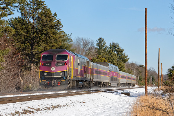 """Along the straightaway in Shirley MA, an inbound commuter train passes the newest additions to the """"T""""/Pan Am right of way - new telephone poles to carry fiber optic cables. It seems like we just got rid if the old code lines and poles... 12/14/2017 - 598C4961dK"""