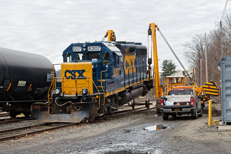 """""""...Glad we've got triple A...""""<br /> CSX GP40-2, no. 6207 broke an axle yesterday as it crossed the diamond at MP83 in Palmer MA. She was dragged onto one of the siding tracks in the CSX yard in Palmer for repairs and she's been hanging in the air for a while as the repair crew waits for parts to come from Selkirk.<br /> 12/8/2017 - 598C4799dK"""