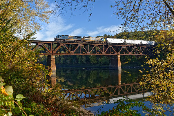 Led by a pair of the brand-new-used ex-CSX C40-8s, Pam Am train ED-9 crosses the iron bridge that spans the Connecticut River at the east end of the East Deerfield yard.<br /> 10/19/2017 - 598C4133dK