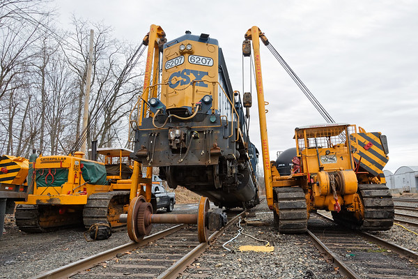 """""""...Glad we've got triple A...""""<br /> CSX GP40-2, no. 6207 broke an axle yesterday as it crossed the diamond at MP83 in Palmer MA. She was dragged onto one of the siding tracks in the CSX yard in Palmer for repairs and she's been hanging in the air for a while as the repair crew waits for parts to come from Selkirk.<br /> 12/8/2017 - 598C4814dK"""