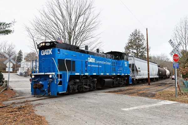Leased by the Grafton & Upton Railroad, EMD GP40 GATX 326 pulls a half dozen cars across Ray St, just south of their yard in Grafton, MA.<br /> 11/30/2017 - 598C4636dK