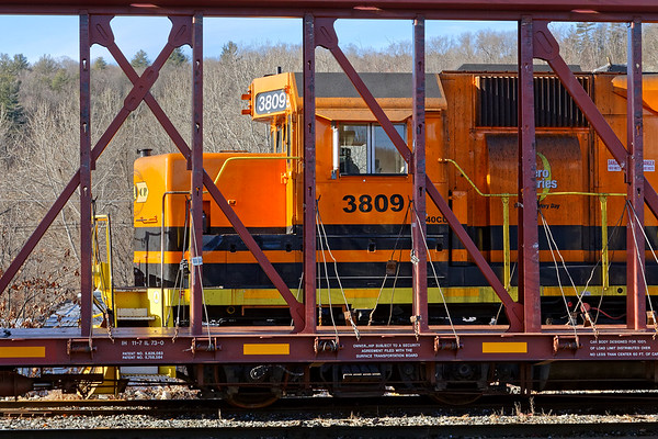 Framed by an empty lumber car, NECR 3809 sits quietly in the early morning sun in the yard at MP83 in Palmer MA. 1/14/18