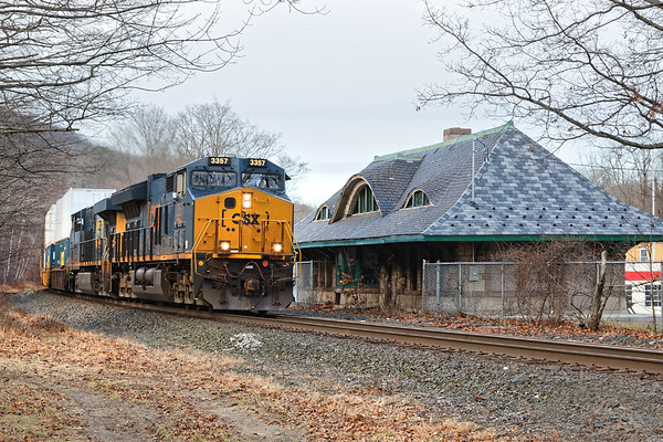 Running at track speed with a long drag of stacks for Worcester, train Q022 passes the historic depot in the center of Warren, MA.<br /> 12/30/2018