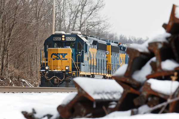 Train B740 eases past a pile of scrap track in the CSX yard at MP83 in Palmer MA. 2/9/2018