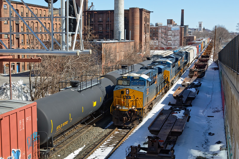 With 426 holding on the other track, train Q427 heads west out of Worcester past the old Crompton & Knowles factory buildings near Grand St.<br /> 3/19/2018