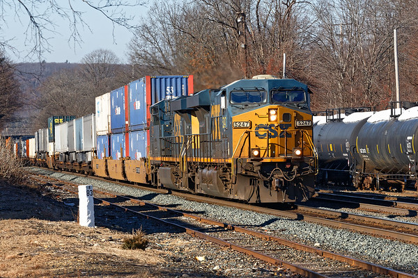 CSX train Q022 eastbound into the warm morning sun at MP83 in Palmer MA.<br /> 12/10/2018