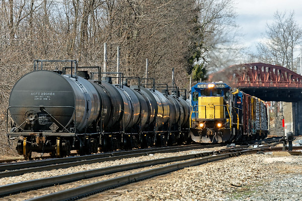 In Ayer, train EDPO slowly eases out from under the Main St bridge and past a cut of tank cars on it's way to Portland.<br /> 4/26/2018
