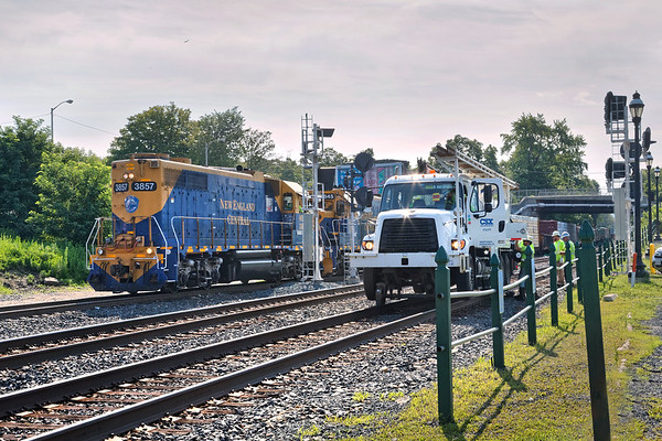At MP83 in Palmer MA, a CSX crew replaces a section of rail on the main as NECR units 3857 and 3845 pull a cut of cars out of the yard.<br /> 7/30/2018