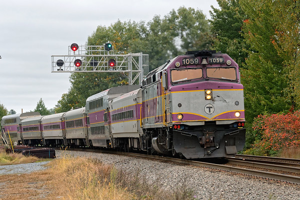 An outbound commuter runs under the new signal gantry just east of the Shirley MA station.<br /> 10/8/2018