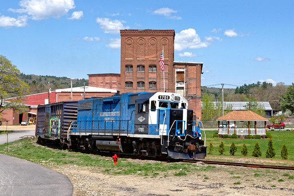 After backing down the hill into the mill complex at South Barre and spotting a couple of cars, 1751 pulls out from between the buildings and heads back to their main.<br /> 5/9/2018