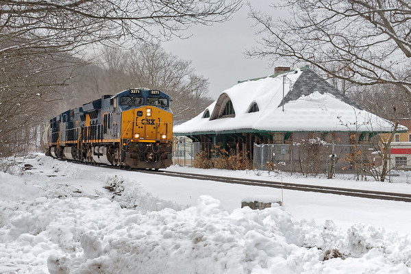 Back to Winter!<br /> Framed by the remnants of our recent 12-18 inch snowfall, CSX train Q426 rolls by the old B&A depot in the center of Warren MA.<br /> 3/9/2018