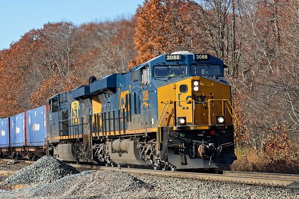 With remnants of Fall foliage in the background, train Q012 claws it's way up the Charlton Hill at MP57 in Charlton MA.<br /> 11/8/2018