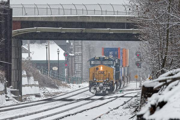 Framed by the Main St. bridge, CSX train Q022 runs through light snow as it passes the depot at MP83 in Palmer MA. 1/17/2018