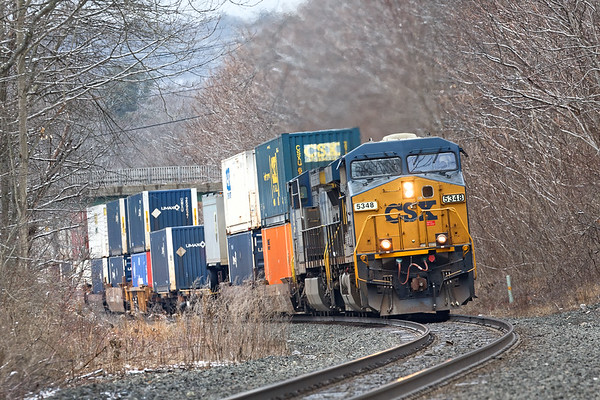 As CSX train Q022 climbs the grade near MP75 in West Warren MA, the light powdered sugar coating of snow on the trees reminds us that it's still winter despite the recent record high temperatures.<br /> 2/23/2018
