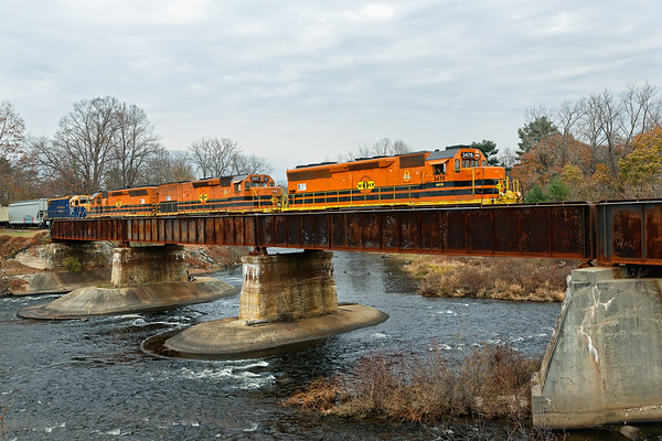 After dropping cars at Barretts, NECR train 611 crosses the bridge at Three Rivers MA.<br /> 11/11/2019