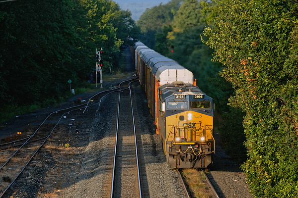 Train Q264  runs into the early morning sun at MP64 in East Brookfield MA.<br /> 9/10/2019