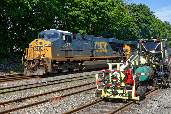 In the Palmer MA yard, MOW equipment sits quietly on the rip track as train Q022 rolls by.<br /> 6/17/2019
