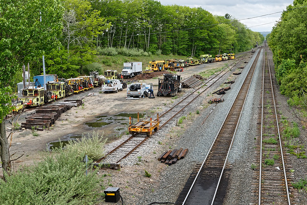 A conga line of track equipment is tied down in the yard at MP64 in East Brookfield MA.<br /> 5/24/2019