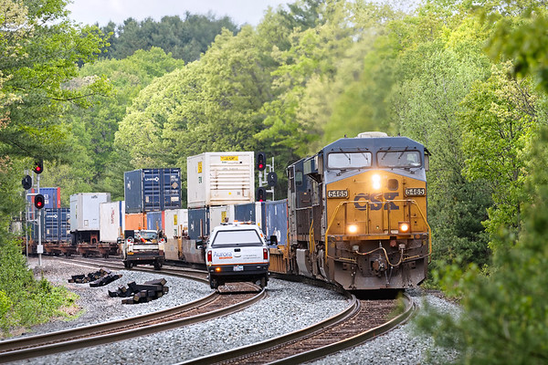 Framed by lush late Spring foliage, two westbound track cars hold the main as a very short Q022 crosses over onto the siding at MP60 in Spencer MA.<br /> 5/24/2019