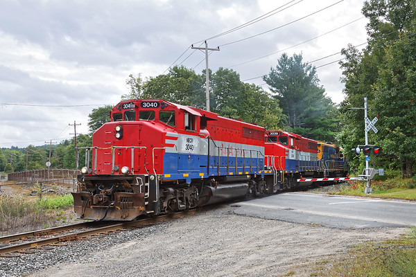 After dropping it's train just before the crossing, NECR train 608 light power crosses Hospital Road at the south end of their yard in Palmer MA.<br /> 9/4/2019