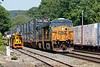 CSX train Q022 rolls past a line of MOW equipment in the yard at MP83 in Palmer MA.<br /> 6/12/2019