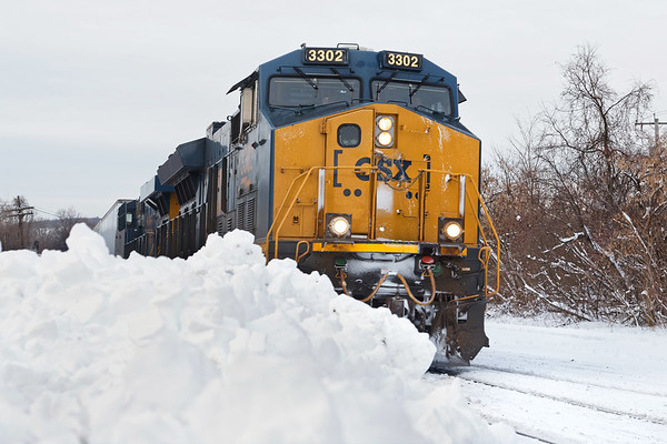Our first serious storm of the year left one to two feet of snow throughout New England. Running past the snow piles in Palmer, Q012 heads to Worcester with a long drag of stacks.<br /> 12/4/2019