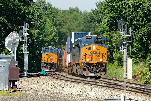 At MP57 in Charlton MA, train Q426 holds the main as train Q022 runs by on the siding with a short drag of stacks for Worcester.<br /> 6/28/2019