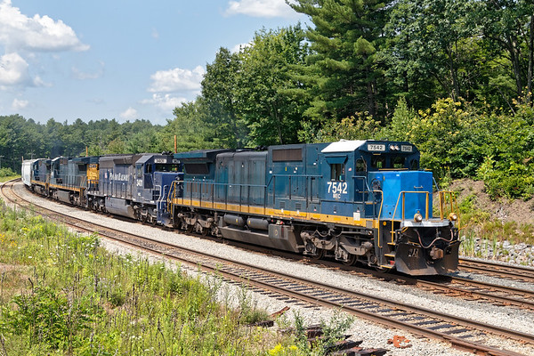 "Led by MEC 7542 (Smurf Nose), train ED-8 eases down the hill past the Wachusett ""T"" station in Fitchburg MA.<br /> 7/25/2019"