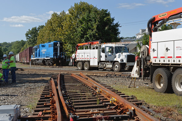 Mass Central eases down the yard lead into the CSX yard at MP83 as work continues at the diamond.<br /> 8/26/2019