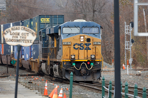 View from across the parking lot - train Q022 slams across the diamond at MP83 in Palmer MA.<br /> 11/14/2019
