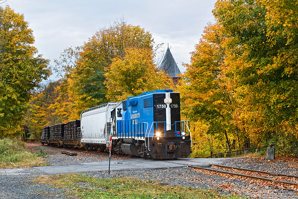 Framed by some of the brightest foliage on it's route, Mass Central 1750 rolls past the old mill in Gilbertville with a load of pipe for South Barre.<br /> 10/8/2019