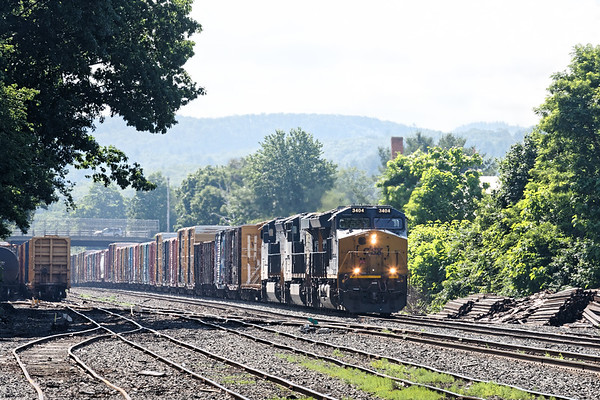 On a hazy hot summer morning, train Q427 eases through the CSX yard at MP83 in Palmer MA.<br /> 6/26/2019