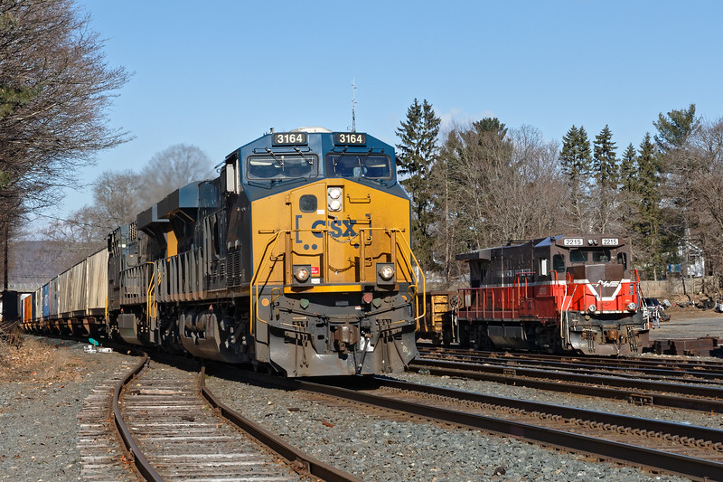 P&W 2215 sits tied down on the rip track as CSX train Q022 blasts through the yard at MP83 in Palmer MA.<br /> 3/18/2019
