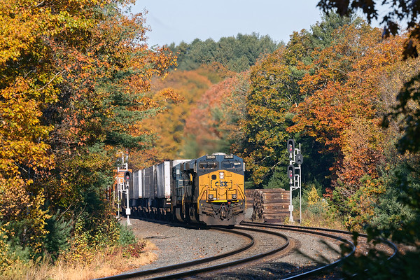 Against a backdrop of warm Fall color, CSX train Q012 runs through the S-curves at MP60 in Spencer MA.<br /> 12/21/2019