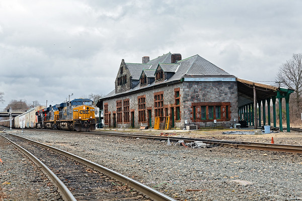 A long Q263 approaches the historic Palmer MA depot.<br /> With the trend towards longer auto trains with DPUs stuck in the middle, the westbound empties are longer as well. On 4/10, Q263 was over 10,000 feet long with two CSX units and a CN on the point and a CSX DPU about halfway back.<br /> 4/10/2019
