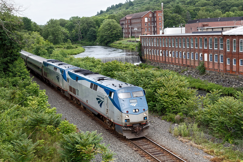 With Amtrak 101 and 177 running elephant style, train 449 rolls past the Wright's mill complex and dam near MP75 in West Warren MA.<br /> 7/18/2019