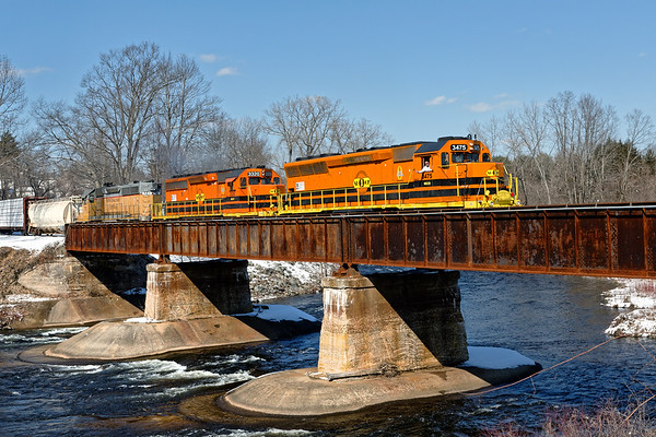 With a friendly wave from the engineer, NECR train 611 crosses the bridge in Three Rivers MA with NECR 3475 leading NECR 3320 and 721.<br /> 3/5/2019