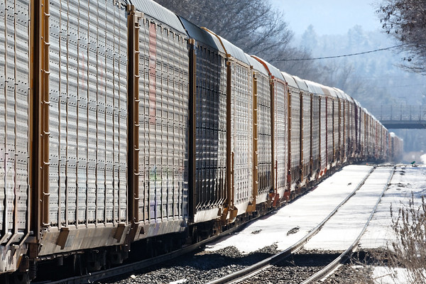 Automobiles from here to there!<br /> At MP83, a very long Q264 eases down the siding waiting for Q022 to leapfrog ahead on the main.<br /> 3/13/2019