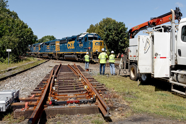 Work on installation of the PTC mandated derail switches pauses as B740 eases across the diamond with 4 units and a long train.<br /> 8/26/2019