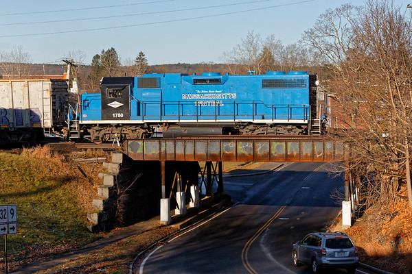 Bathed in warm early morning light, MCER 1750 runs long hood forward over the Main St. bridge in Ware MA.<br /> 11/21/2019