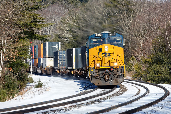 Almost Spring, almost bare ground - train Q022 rounds the S-curves at MP60 in Spencer MA.<br /> 3/3/2019