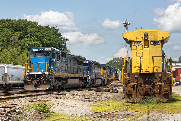 Pan Am train ED-8 pulls through the Gardner MA yard past 7595 which has been sitting on the RIP track after crapping out a few days ago.<br /> 7/25/2019