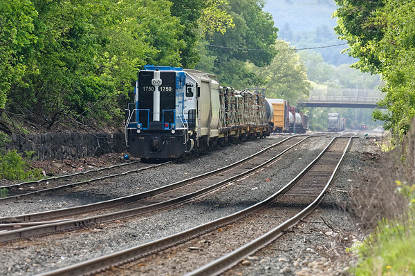 Mass Central 1750 pulls a load of pipe out of the CSX yard at MP83 in Palmer MA. In the distance to the far right is the FRED on Q012 which just went through on the main.<br /> 5/24/2019